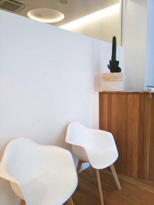 Sala de espera en tonos claros y mostrador en madera roble.